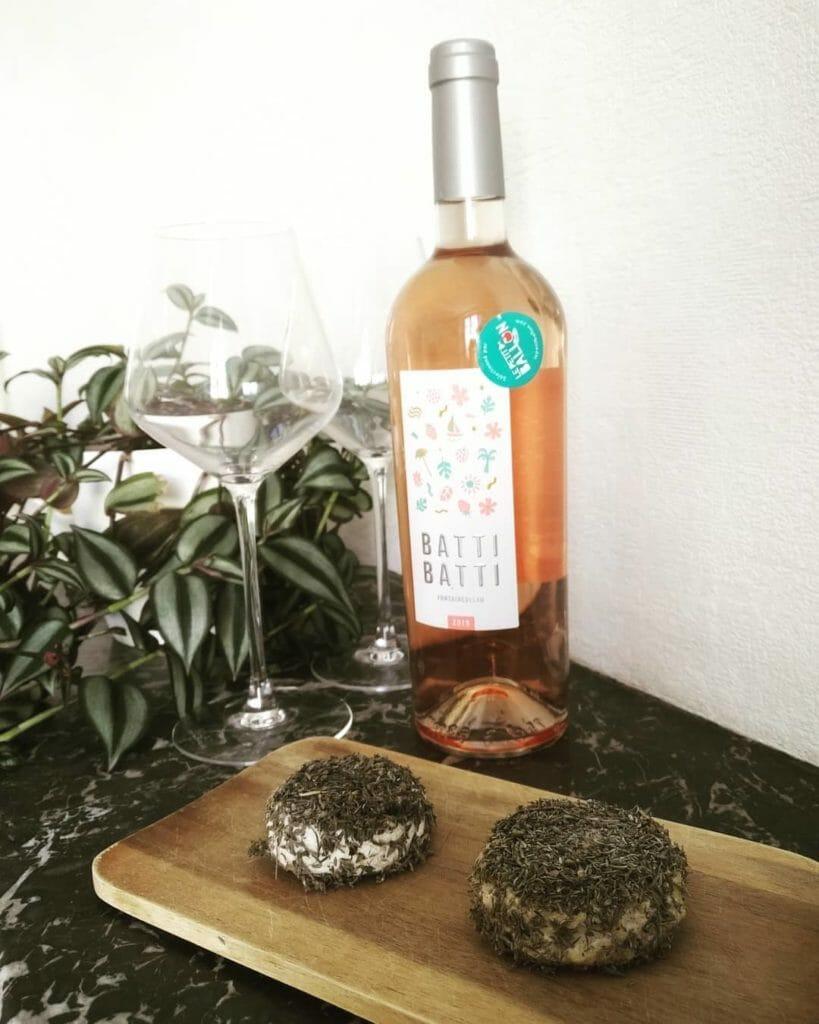 fromage de chèvre maison aux herbes sur planche en bois et bouteille de rosée